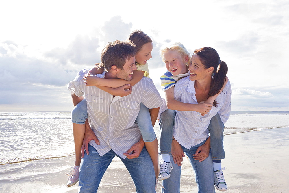 Parents Giving Children Piggybacks On Beach Vacation