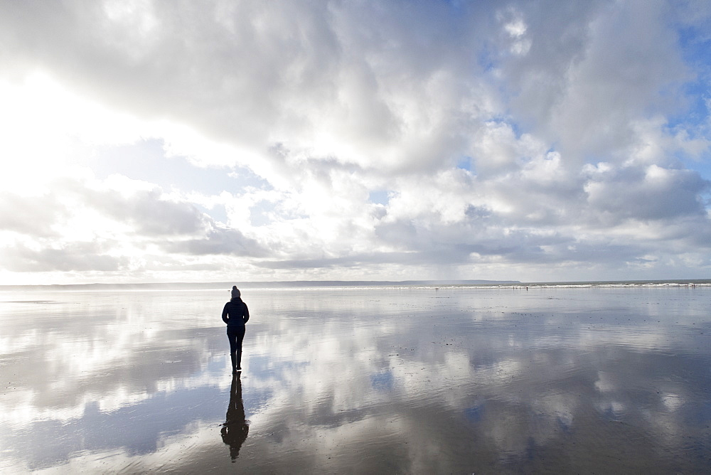 Silhouette reflection solitary woman standing on wet ocean beach at low tide below clouds