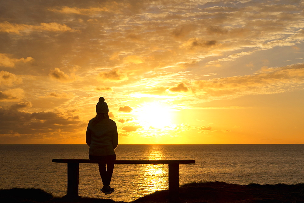 Silhouette solitary woman on bench looking at tranquil sunset view over ocean - 786-10299