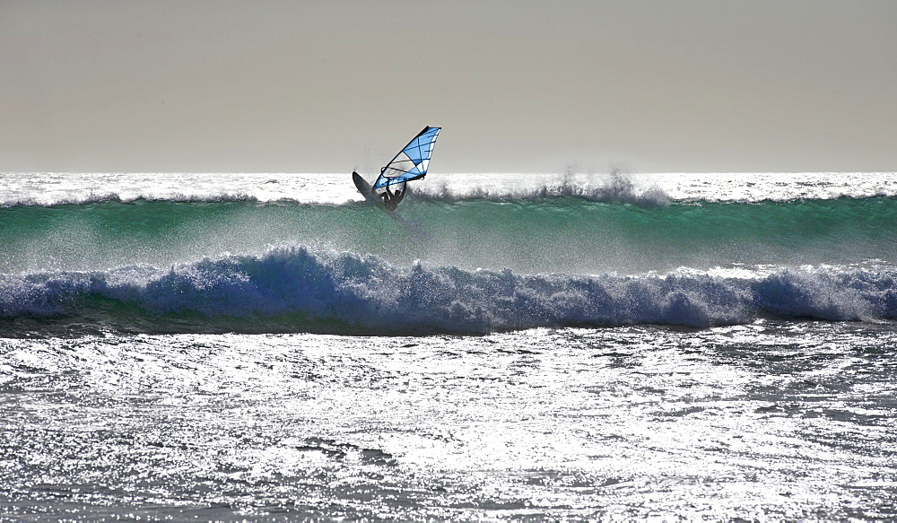 Windsurfer windsurfing on sunny windy ocean jumping wave