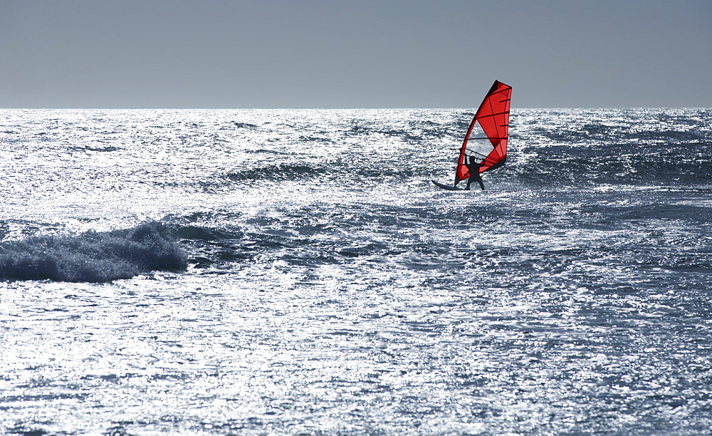 Windsurfer windsurfing on sunny windy ocean