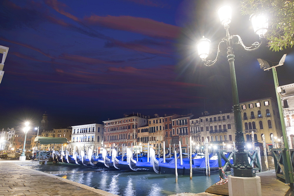 Streetlights shining over covered moored gondolas along architectural buildings in the Grand Canal at night, Venice, Italy