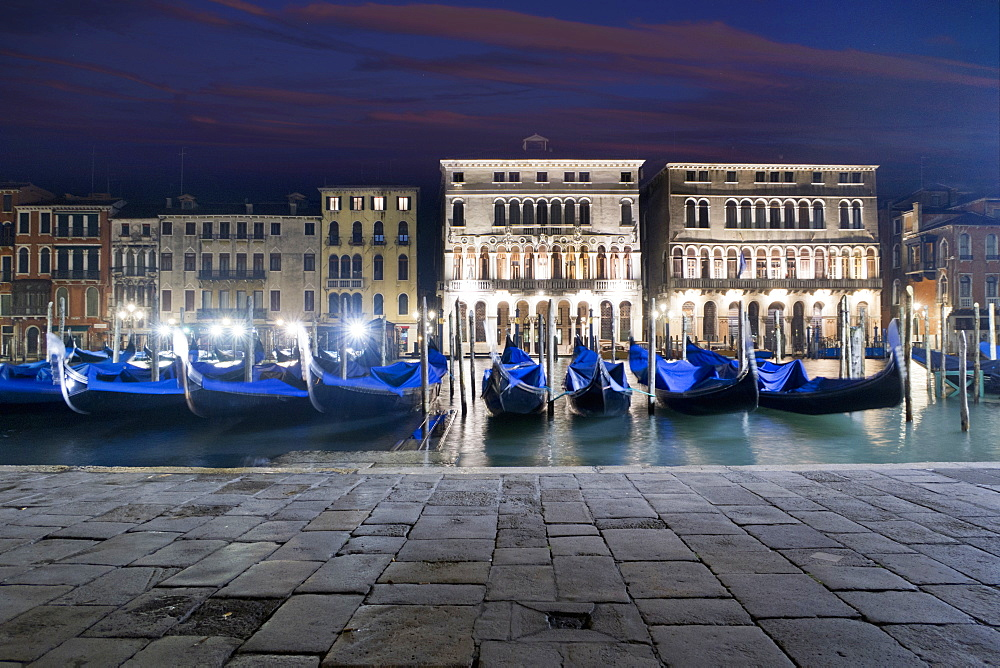 Covered moored gondolas in front of illuminated architectural buildings in the Grand Canal at night, Venice, Italy