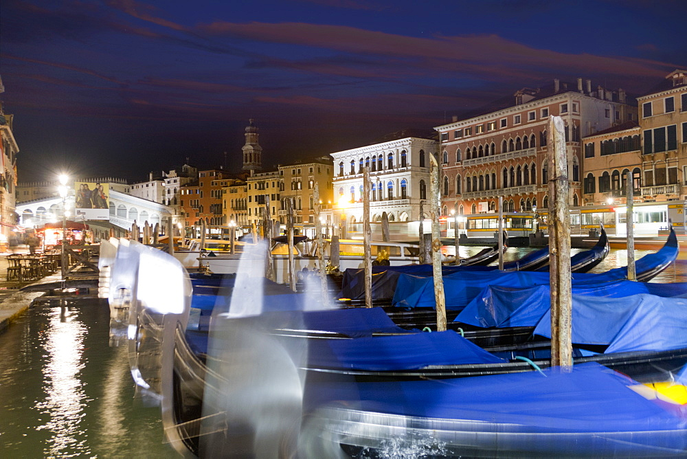 Covered moored gondolas in front of illuminated architectural buildings in the Grand Canal at night, Venice, Italy - 786-10306