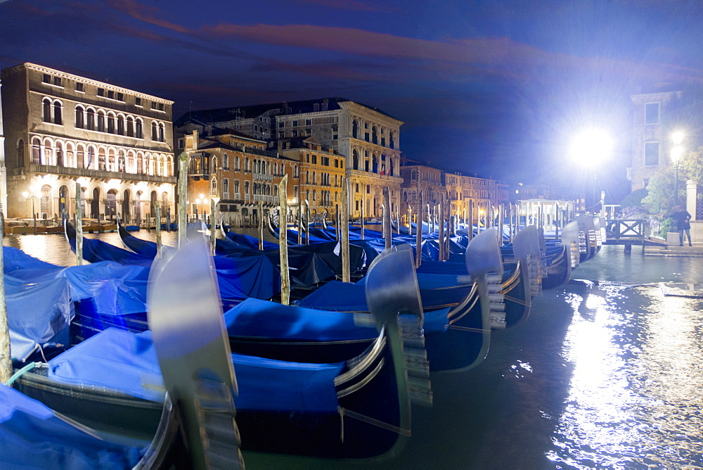 Streetlight shining over covered moored gondolas along architectural buildings in the Grand Canal at night, Venice, Italy - 786-10307