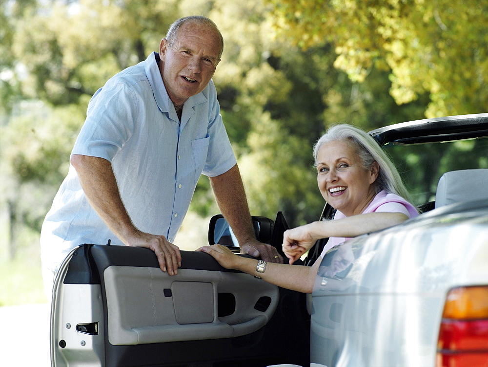 Senior couple posing beside convertible car, woman sitting in driver's seat, smiling, portrait
