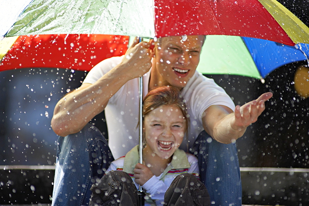 Father and daughter (9-11) sitting on steps in rain beneath large umbrella, smiling, portrait - 786-1249