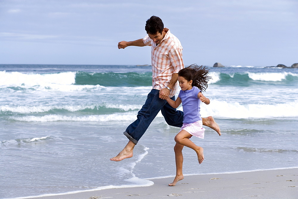 Father and daughter (6-8) skipping on beach near water's edge, side view