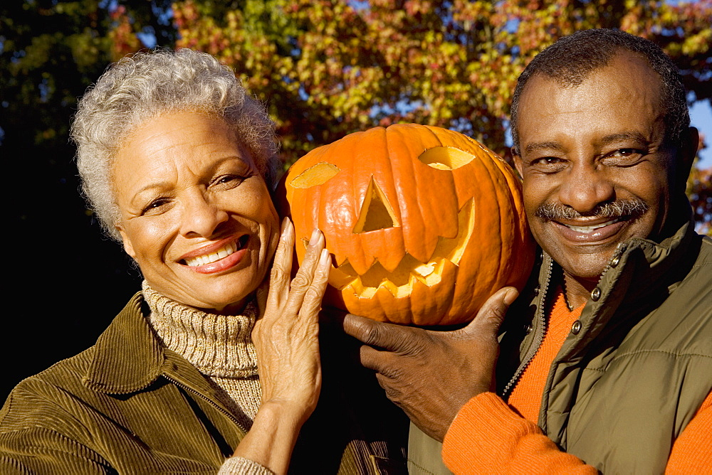 Senior couple holding aloft Jack O'Lantern pumpkin, smiling, front view, close-up, portrait