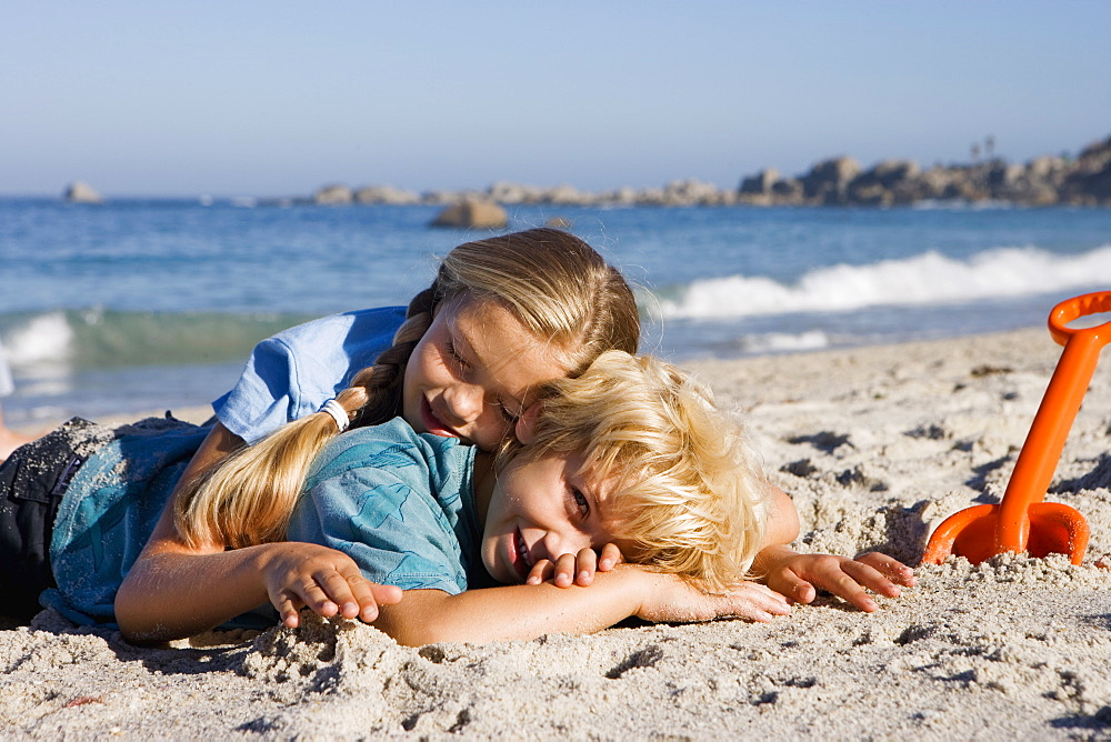 Boy (4-6) and girl (7-9) lying on sandy beach beside orange spade, smiling, side view