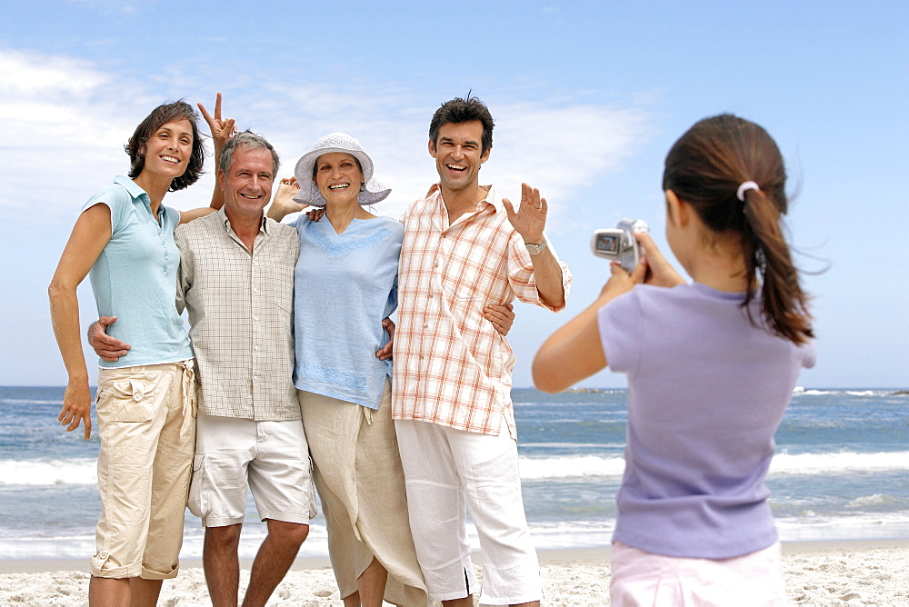 Girl (7-9) photographing three generation family on beach, posing and smiling, sea in background