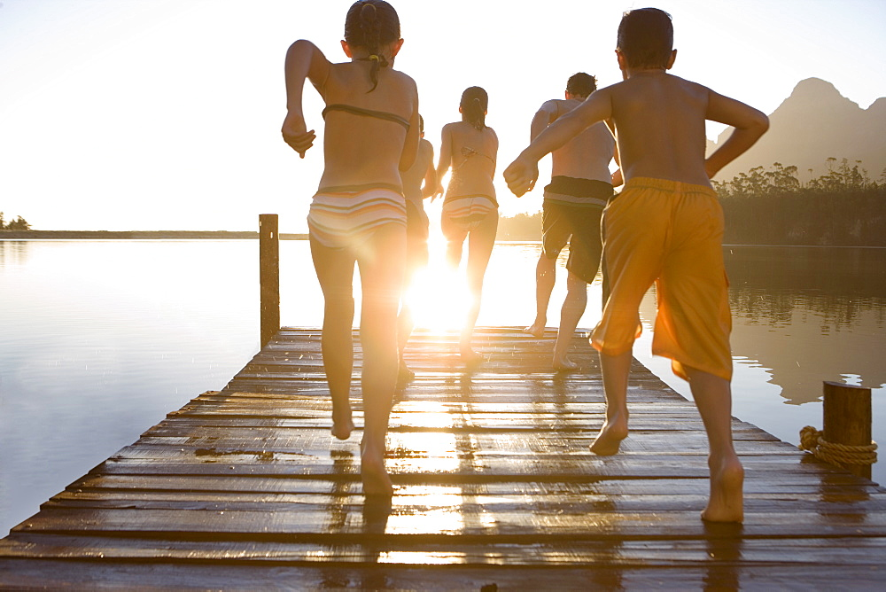 Family, in swimwear, running along jetty, jumping into lake at sunset, rear view (lens flare) - 786-2072