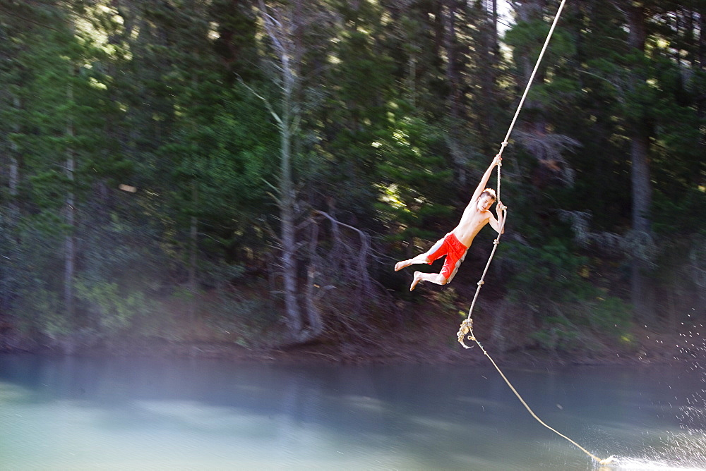 Boy (9-11), in swimming shorts, swinging on rope above lake