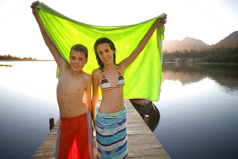 Teenage boy and girl (12-14) standing on lake jetty at sunset, holding aloft green towel, smiling, portrait