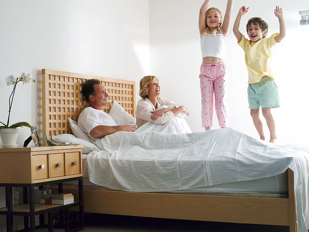 Parents lying in double bed at home, two energetic children (5-8) jumping up and down on bed, smiling