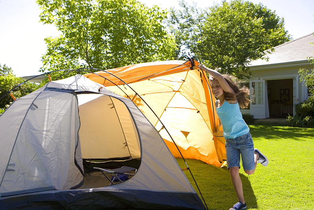 Energetic girl (8-10) assembling dome tent on garden lawn, positioning outer orange canvas over tent, smiling