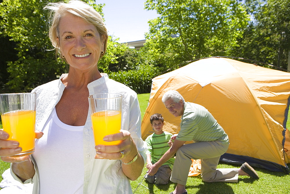 Boy (8-10) and grandfather assembling dome tent on garden lawn, focus on grandmother serving orange juice in foreground, smiling, portrait