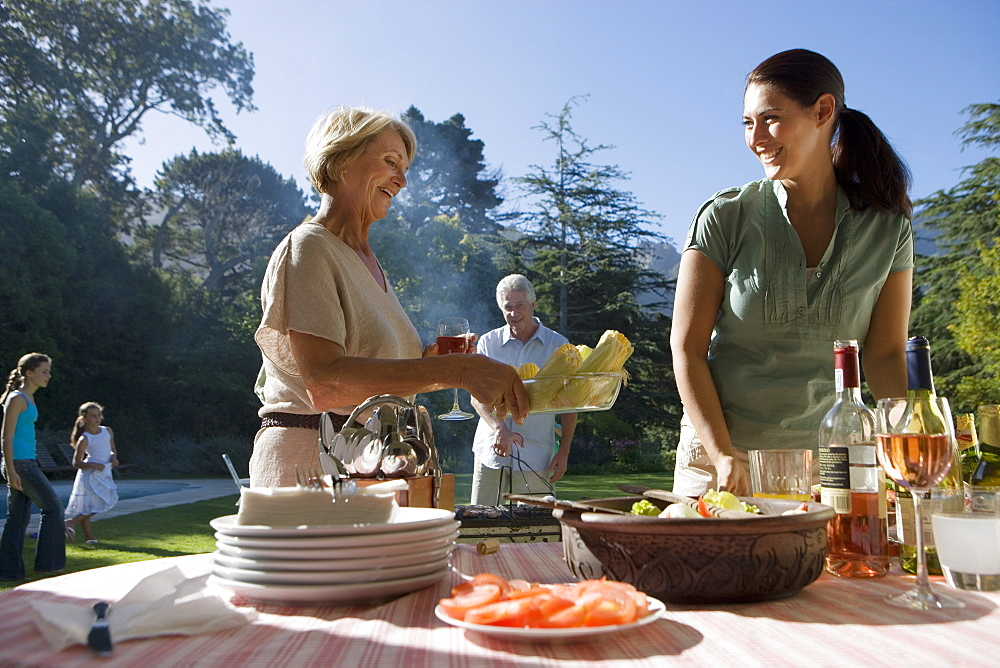 Senior woman passing corn cobs to adult daughter at family barbecue in garden, smiling