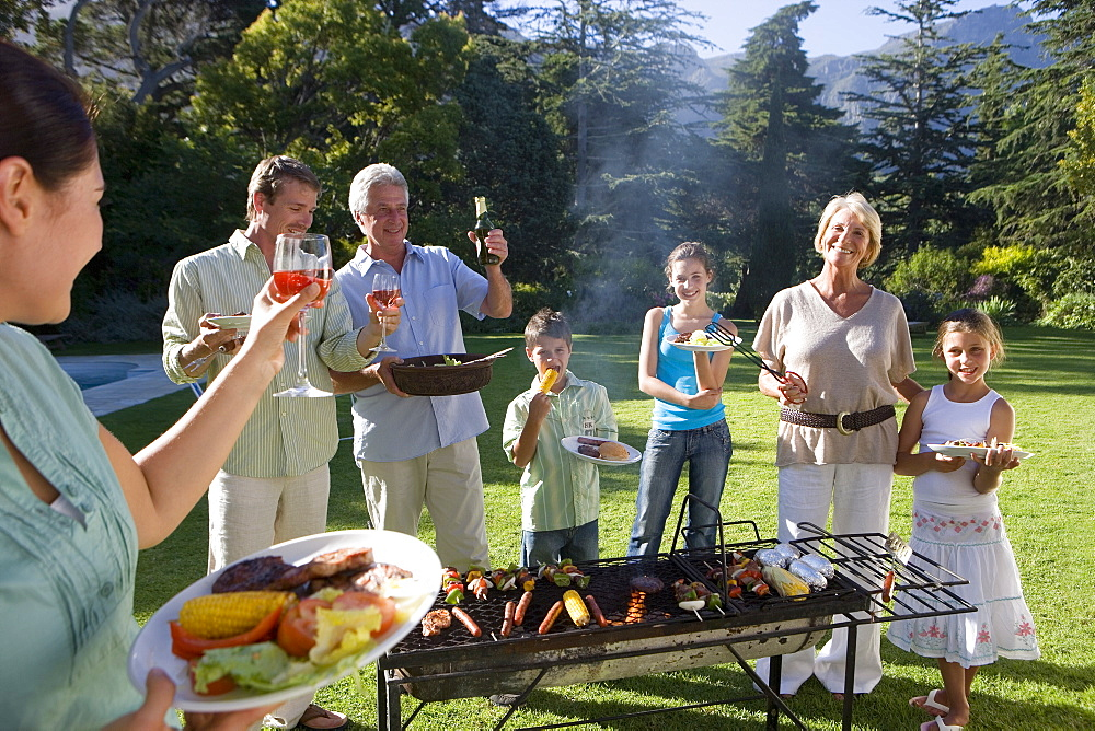 Three generation family standing beside barbecue grill in garden, adults raising wine glasses in toast, smiling