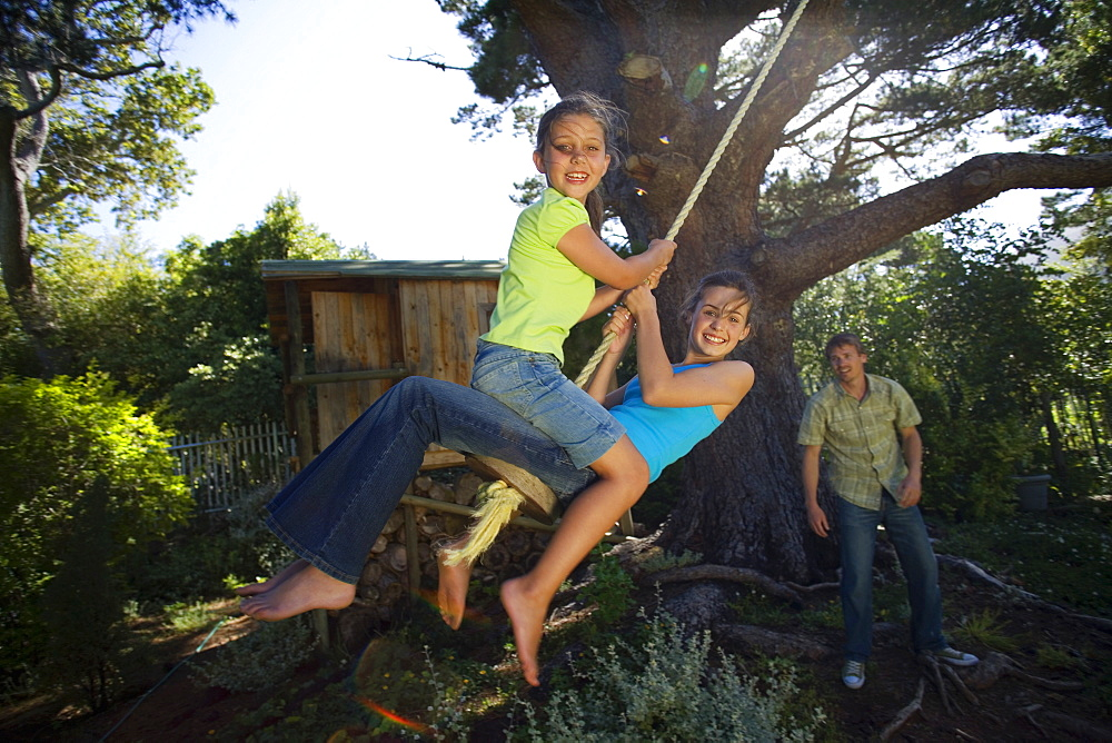 Two girls (8-13) swinging on garden rope swing near tree house, father pushing in background, smiling, portrait