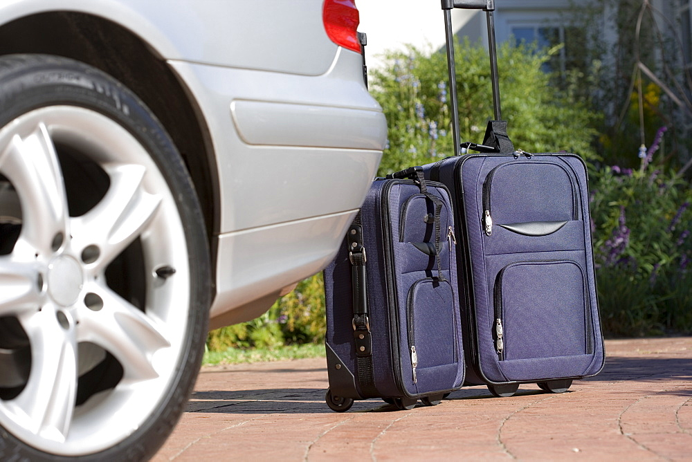 Two suitcases on wheels beside parked car on driveway (surface level)