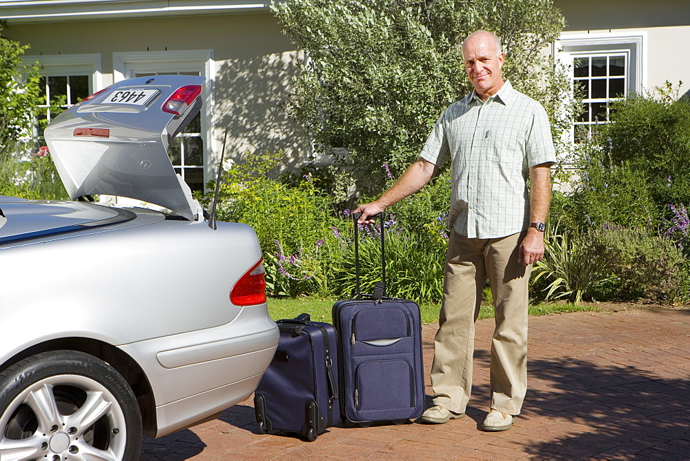 Senior man unloading suitcases on wheels from parked car boot on driveway, smiling, portrait