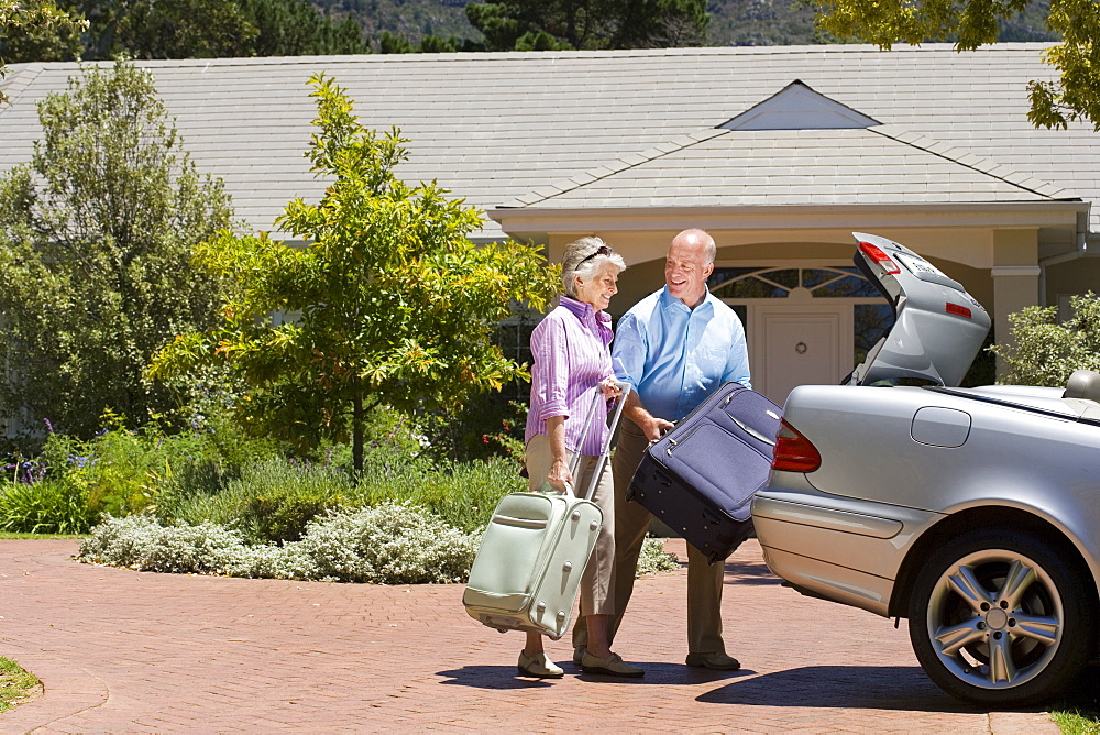 Senior couple loading suitcases into parked car boot on driveway in front of house, smiling, side view