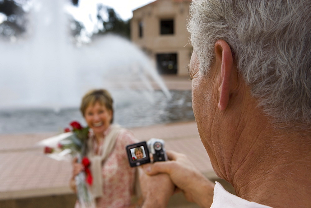 Senior woman standing beside fountain, holding bouquet of red roses, smiling, focus on man filming her with portable video recorder in foreground