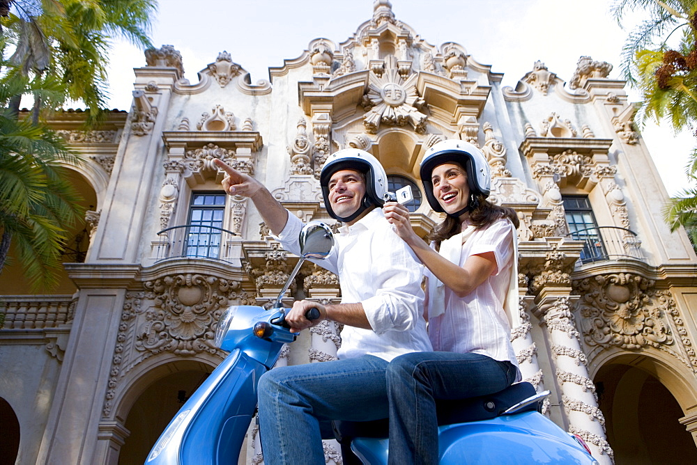 USA, California, San Diego, Balboa Park, couple riding on blue motor scooter, woman filming with portable video recorder, smiling, side view, low angle view