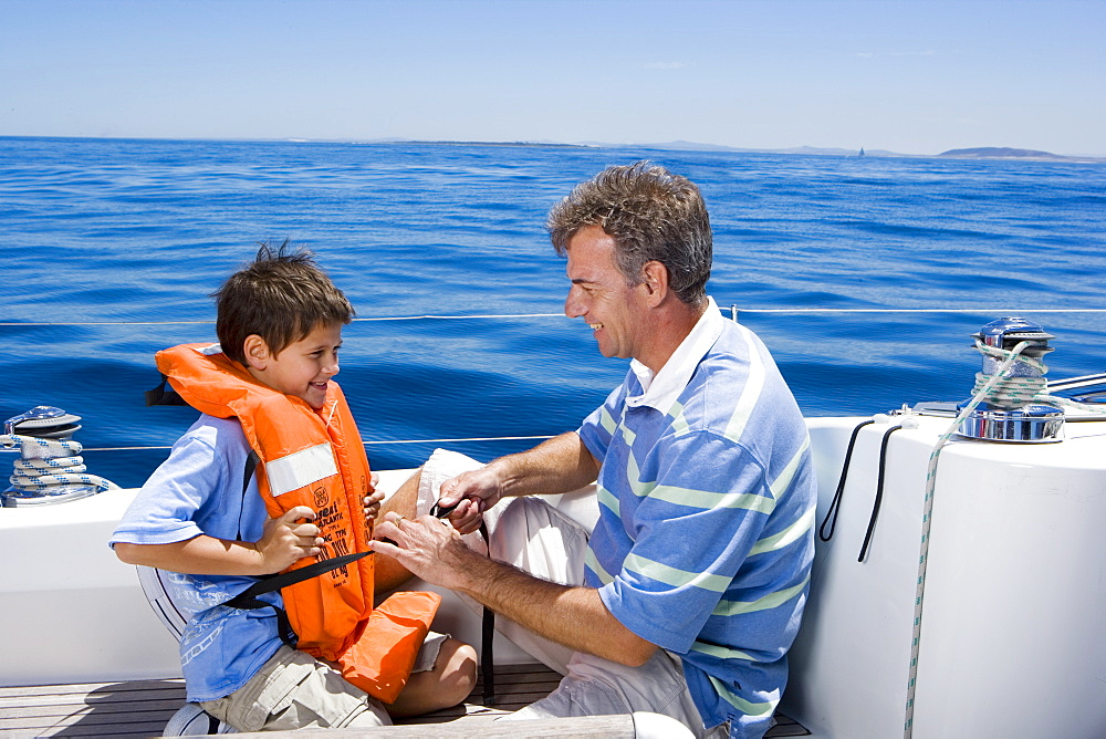 Father and son (8-10) sitting on deck of sailing boat out at sea, boy wearing orange life jacket, man tying strap, smiling, side view