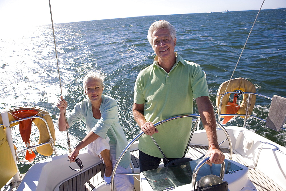 Mature couple sailing out at sea, man standing at helm of yacht, steering, woman sitting at stern, smiling, front view, portrait (backlit)