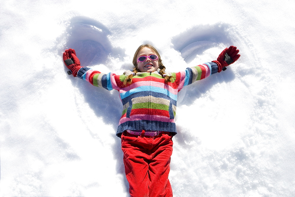 Girl (7-9) lying in snow making 'angel wings', smiling, overhead view - 786-2974