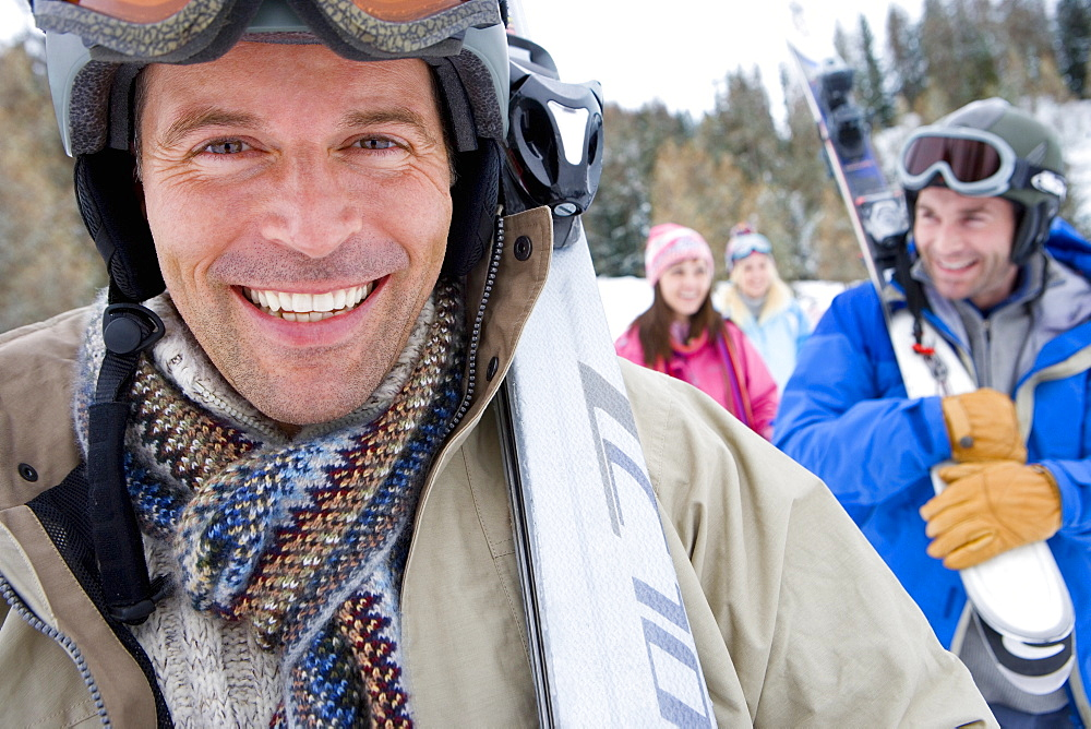 Man in snow field, wearing goggles on head, smiling, portrait, close-up, friends in background