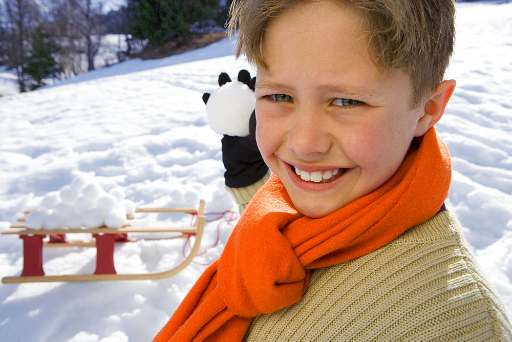 Boy (7-9) holding snow ball in snow field, smiling, portrait, close-up, sled in background