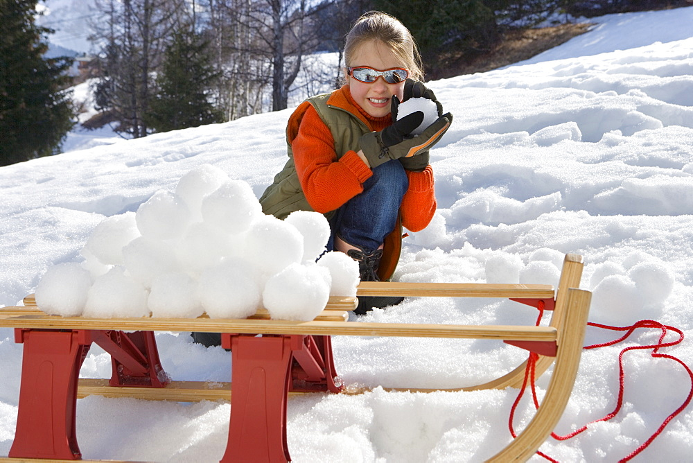 Girl (7-9) making snow ball pile on sled in snow field, smiling, portrait