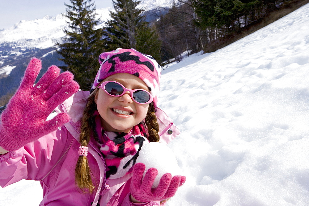 Girl (7-9) wearing woolen hat and sunglasses in snow field, holding snow ball, smiling, portrait - 786-3061