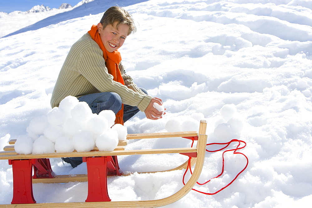 Boy (7-9) crouching in snow by sled and snowballs, smiling, portrait