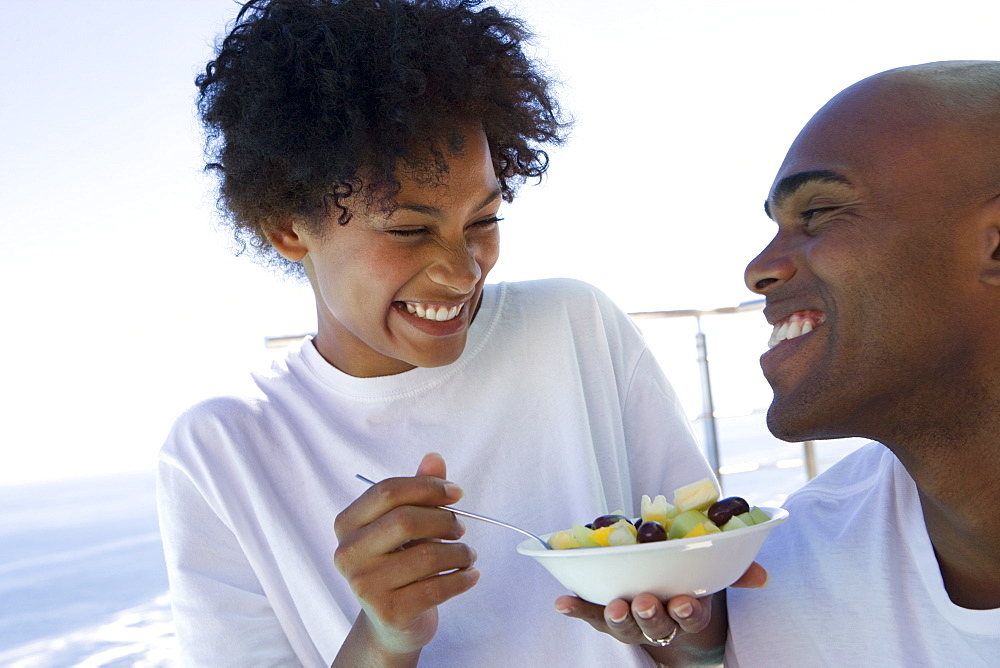 Young couple eating fruit salad outdoors, smiling at each other, close-up