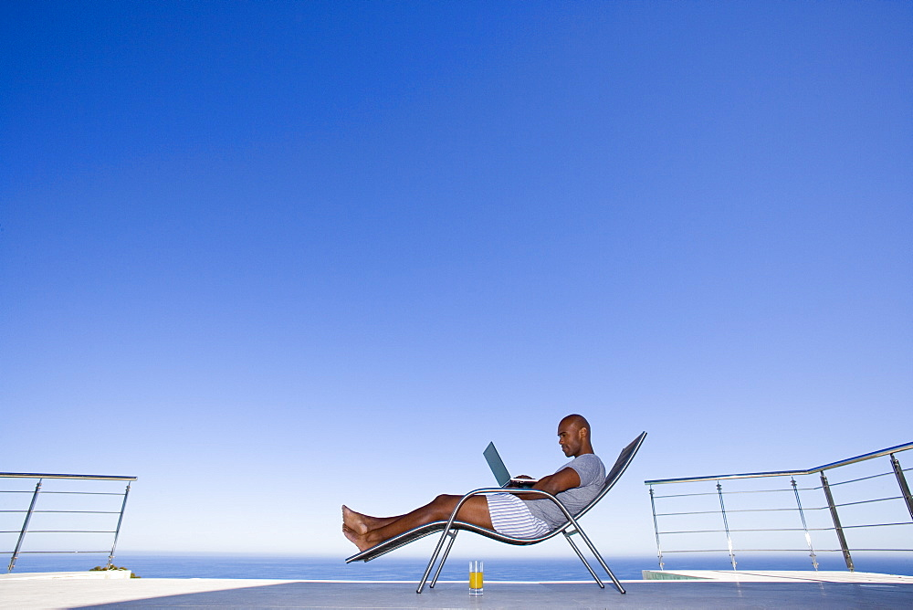 Young man using laptop on deck chair by sea, side view