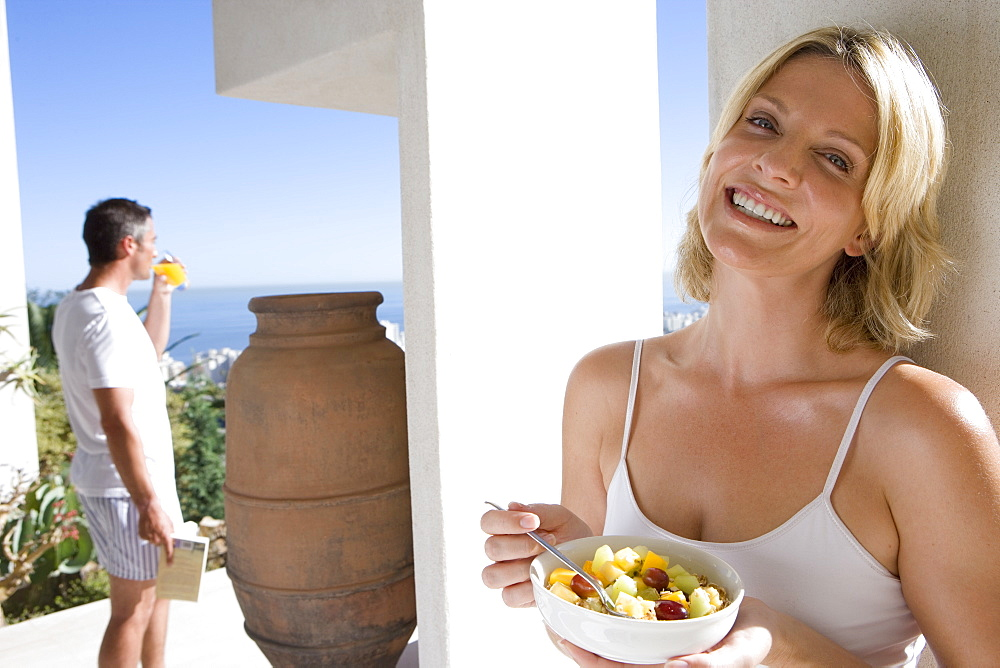 Young woman eating fruit salad outdoors, young man standing in background