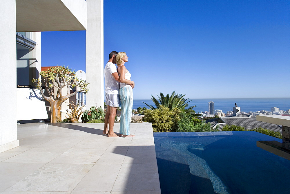 Couple embracing on balcony by swimming pool, side view, sea in background