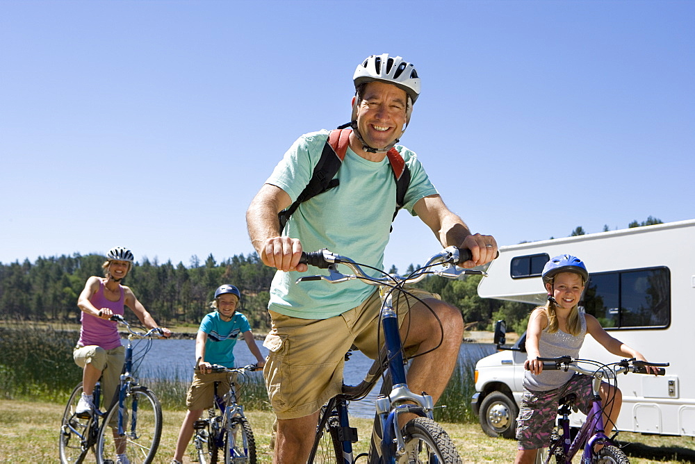 Family of four on bicycles by motor home, close-up of father, low angle view
