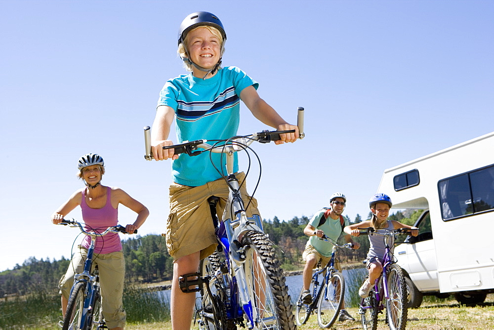 Family of four on bicycles by motor home, close-up of boy (10-12), low angle view