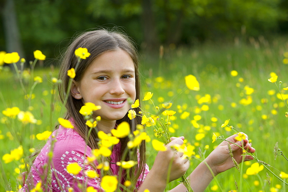 Girl (7-11) in field of wild flowers, smiling