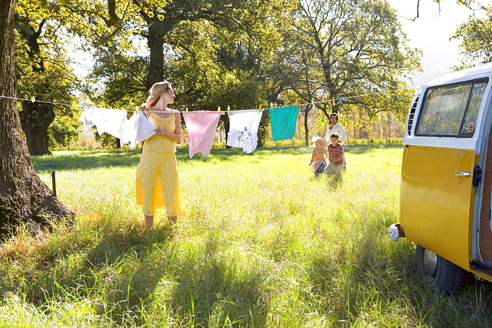 Young woman hanging washing on line by camper van, looking back at family in field