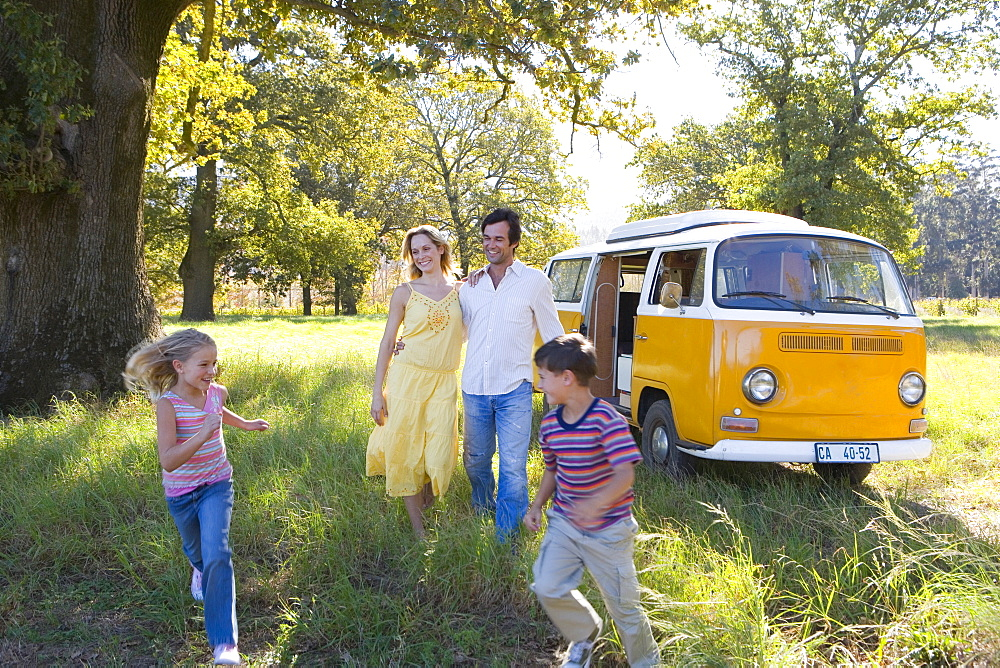 Family of four in field by camper van, son and daughter running (5-9), smiling - 786-3713