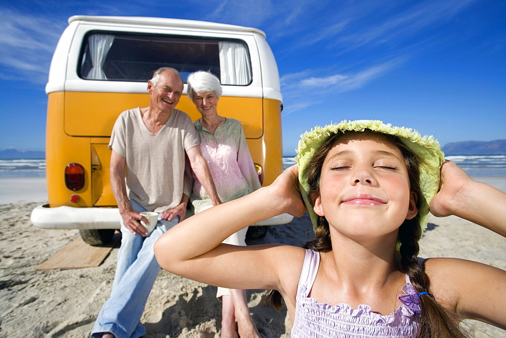 Girl (7-9) holding hat on head on beach by grandparents on back of camper van, smiling, close-up - 786-3785