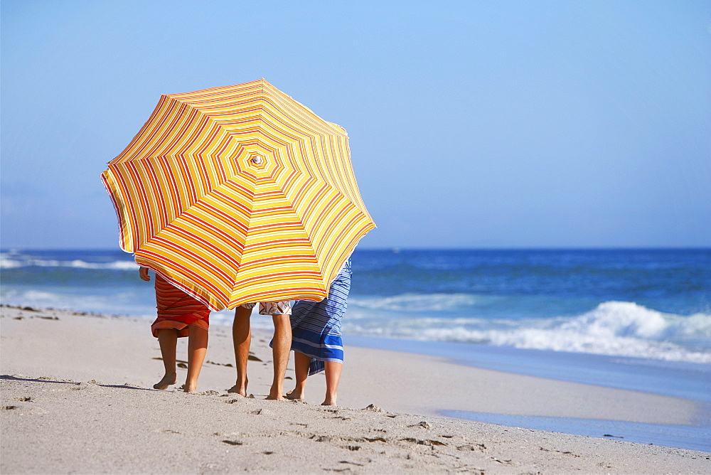 Three friends walking on beach, faces obscured by orange sunshade, rear view, sea in background