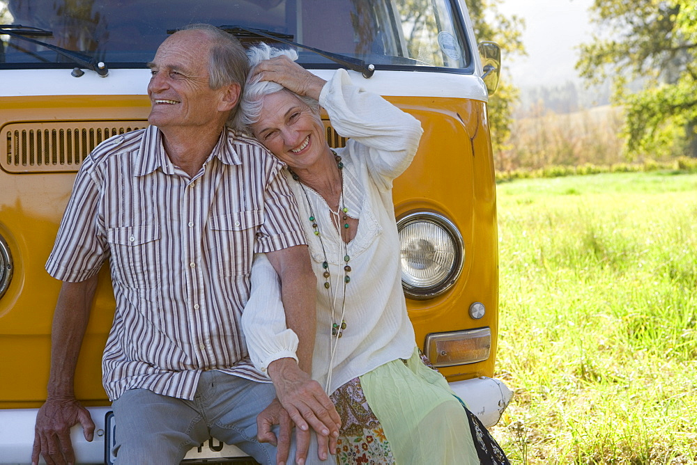 Senior couple sitting on front of camper van, holding hands, portrait of woman, close-up