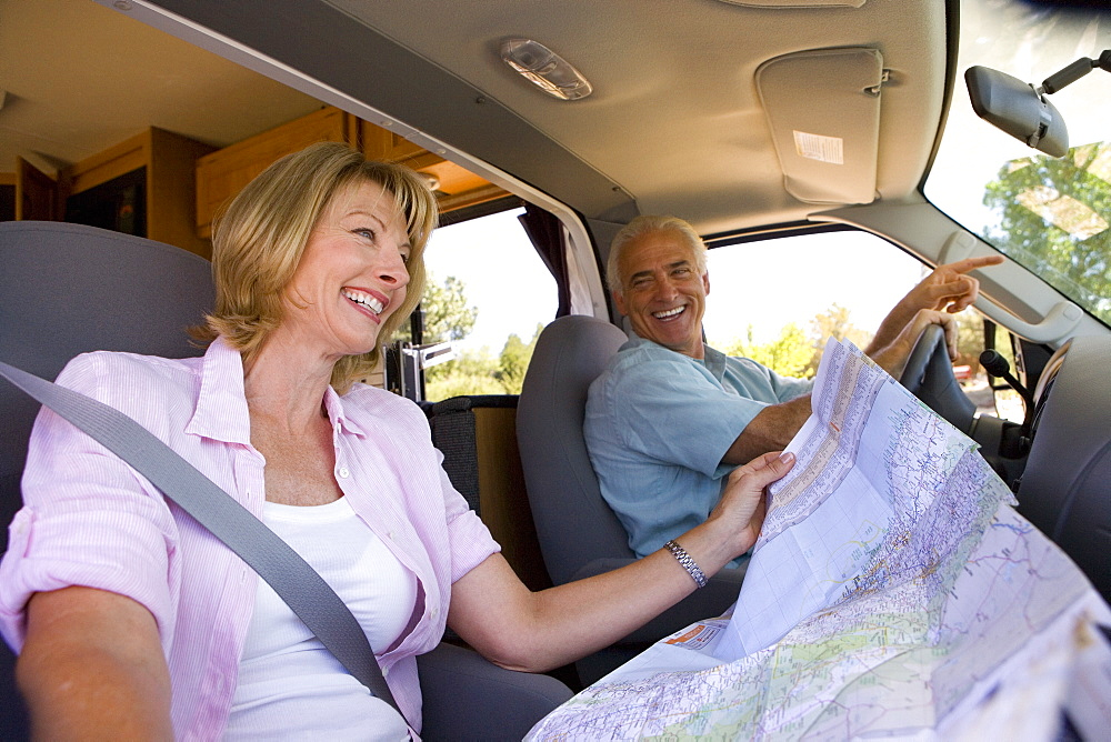 Mature woman with map in motor home by husband, smiling, low angle view - 786-3893